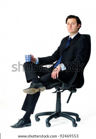 Male office worker seats in his chair, holding a mug of coffee - stock photo