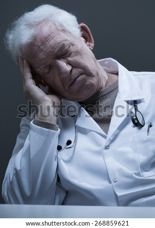Male old doctor sleeping at the desk - stock photo