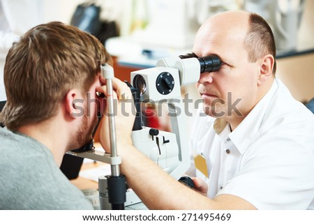 Male optometrist optician doctor examines eyesight of female patient in eye ophthalmological clinic  - stock photo