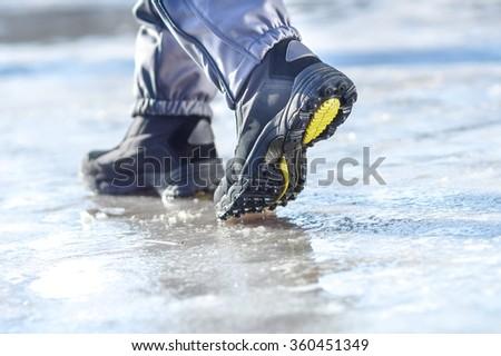 male or female winter boots walking on snowy sleet road - stock photo