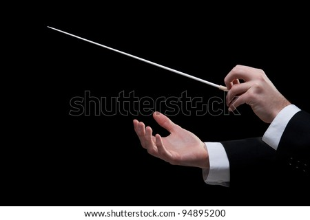 Male orchestra conductor hands, one with baton. Black background. - stock photo
