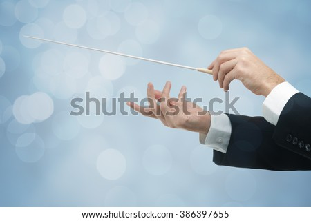 Male orchestra conductor hands, one with baton. Blue background with bokeh. - stock photo