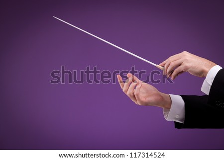 Male orchestra conductor hands, one with baton. Purple background.
