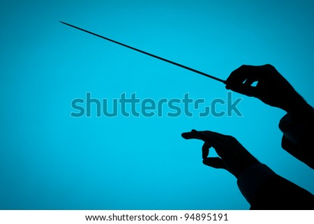 Male orchestra conductor hands, one with baton. Silhouette against blue background. - stock photo