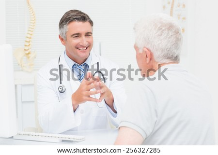 Male orthopedic doctor discussing with senior patient in clinic - stock photo