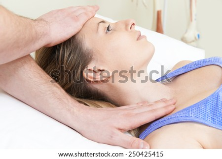 Male Osteopath Treating Female Patient With Neck Problem - stock photo