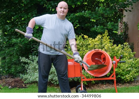 male outside in garden with sand cement mixer - stock photo