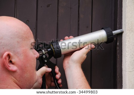 male outside starting repair sealing house door - stock photo