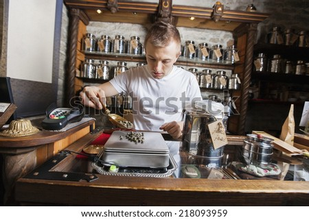 Male owner measuring ingredient on weight scale in tea store - stock photo
