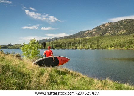 male paddler carrying a red stand up paddleboard and a paddle on a sunny summer day - Horsetooth Reservoir, Fort Collins, Colorado - stock photo