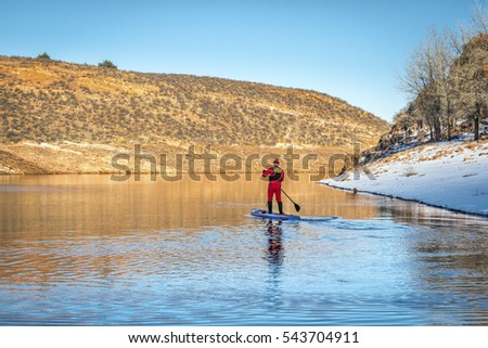 male paddler in red drysuit is paddling a stand up paddleboard on mountain lake in Colorado, winter scenery