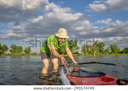 male paddler is washing his SUP paddleboard before starting workout on a local lake in Colorado - stock photo