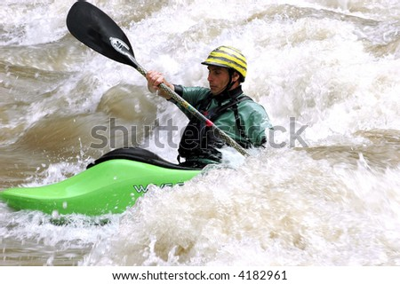 male paddling kayak surfing river wave - stock photo