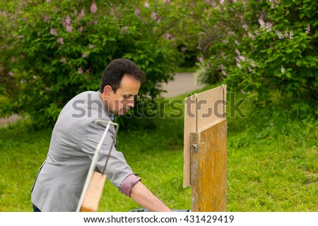 Male painter during creation a masterpiece on a trestle and easel painting with oils and acrylics outdoors - stock photo