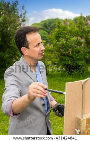 Male painter outdoors looking through the park  working  on a trestle and easel painting with oils and acrylics during an art class - stock photo