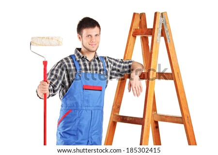 Male painter standing next to a ladder isolated on white background