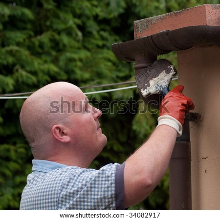 male painting gutter with brush and wearing glove - stock photo
