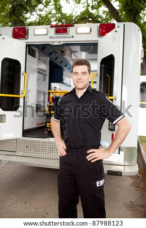 Male paramedic standing in front of ambulance in residential area - stock photo