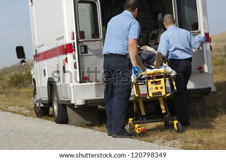 Male paramedics carrying patient on stretcher - stock photo