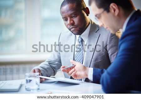 Male partners discussing importrant things - stock photo