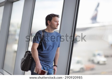 Male passenger at the airport with airplane on background. Middle age businessman holding passport and boarding pass.  - stock photo