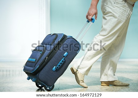 male passenger at the airport with laggage - stock photo