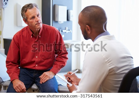 Male Patient And Doctor Have Consultation In Hospital Room - stock photo
