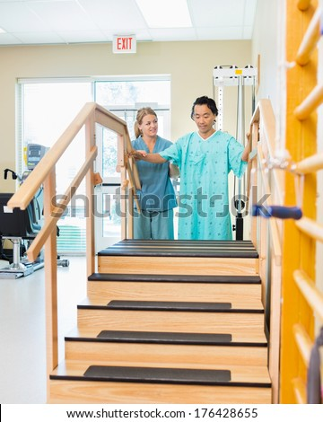 Male patient being assisted by physical therapist in moving upstairs - stock photo