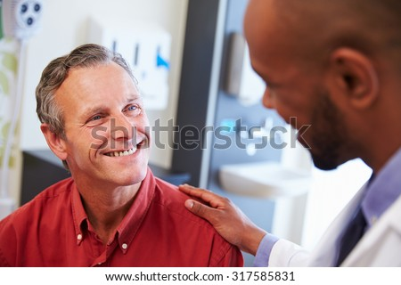 Male Patient Being Reassured By Doctor In Hospital Room - stock photo