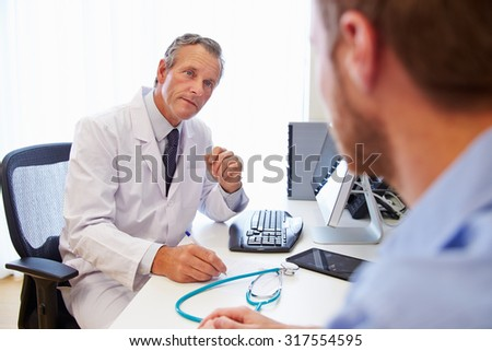 Male Patient Having Consultation With Doctor In Office - stock photo