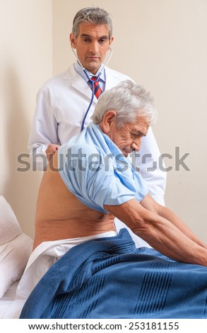 Male patient in 60s undergoing tests at hospital. - stock photo