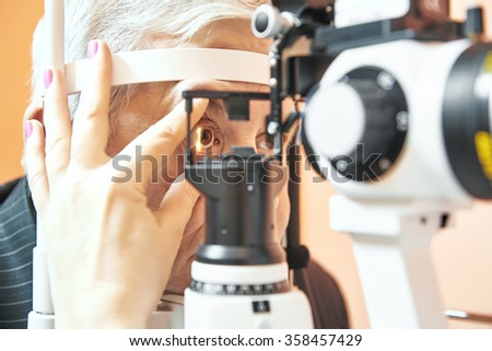 male patient under eye sight examination at ophthalmology clinic - stock photo
