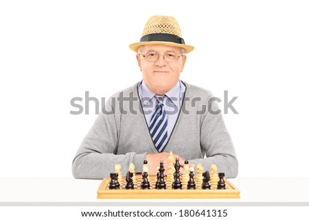 Male pensioner posing behind a chessboard isolated on white background - stock photo