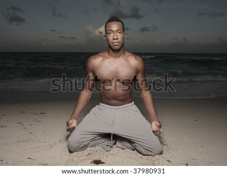 Male performing yoga on the sand