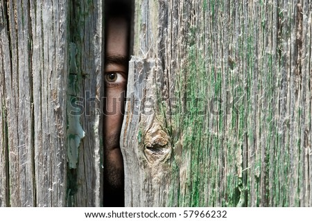 Male person hide behind a wooden wall - stock photo