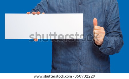 male person holding a white blank sign in blue back - stock photo