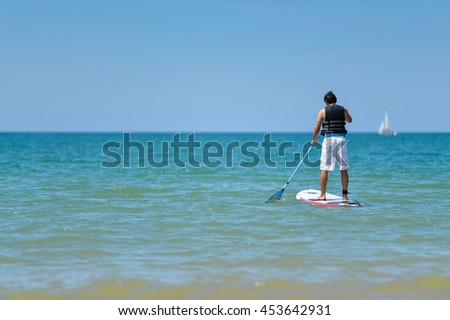 Male person surf paddle boarding, beautiful sunny outdoors background - stock photo
