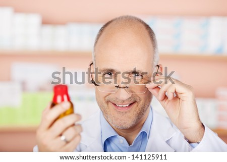 Male pharmacist holding glasses and shows the medicine in pharmacy - stock photo