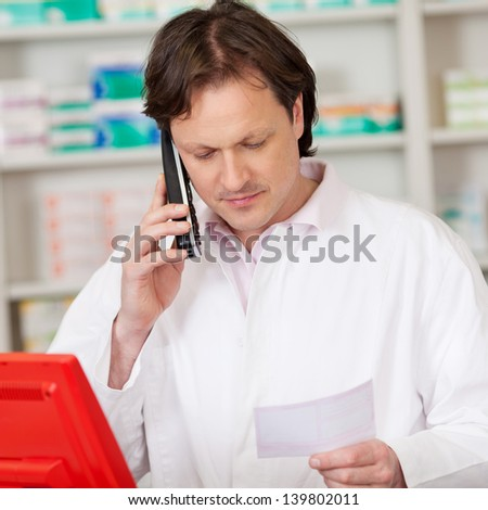 male pharmacist with prescription looking serious while on call - stock photo