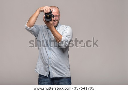 Male photographer focusing and composing an image with his professional digital Dslr camera pointing the lens directly at the viewer - stock photo