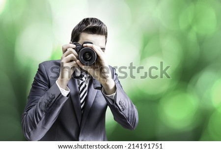 Male photographer focusing and composing an image with his professional digital SLR camera pointing the lens directly at the viewer on green background - stock photo