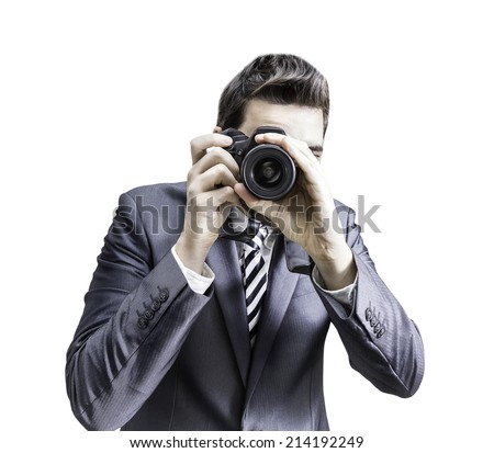 Male photographer focusing and composing an image with his professional digital SLR camera pointing the lens directly at the viewer on white background - stock photo