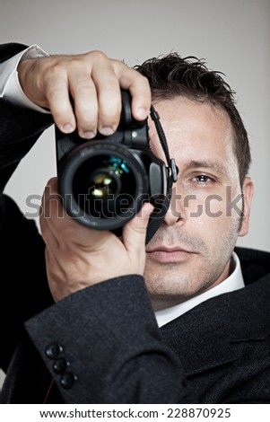 male photographer in business suit taking a picture  - stock photo