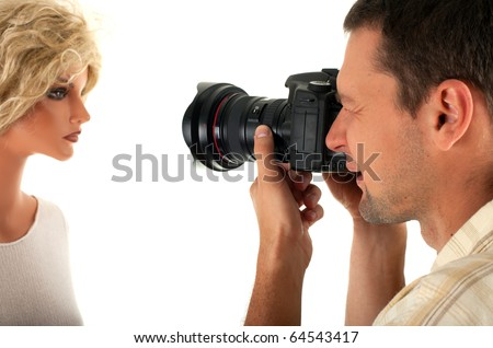 male photographer keeping black digital camera and photographs mannequin
