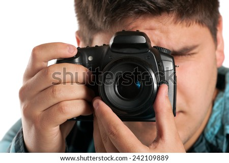 Male Photographer Shooting digital slr camera isolated on white.  Shallow depth of field. - stock photo