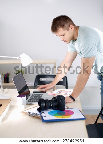 Male photographer standing near  the desk with laptop