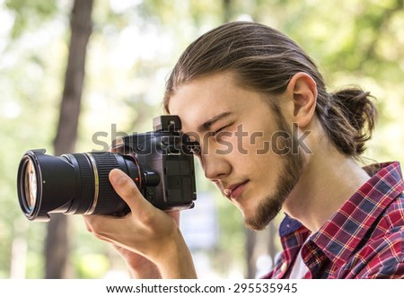 Male photographer taking photos with DSLR digital camera at outdoors. Side view.