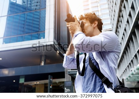 Male photographer taking picture - stock photo