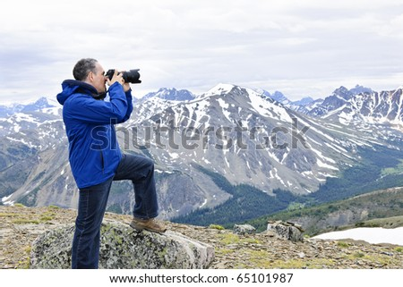 Male photographer taking pictures in Canadian Rocky Mountains in Jasper National Park - stock photo