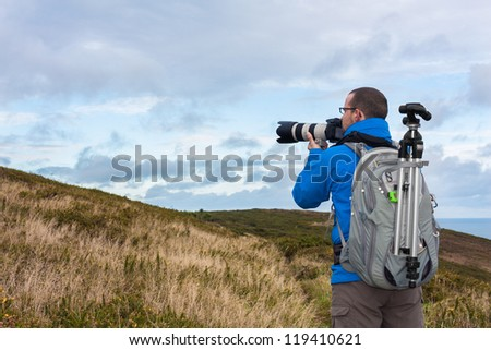 Male photographer with professional equipment is getting ready to take the photo - stock photo